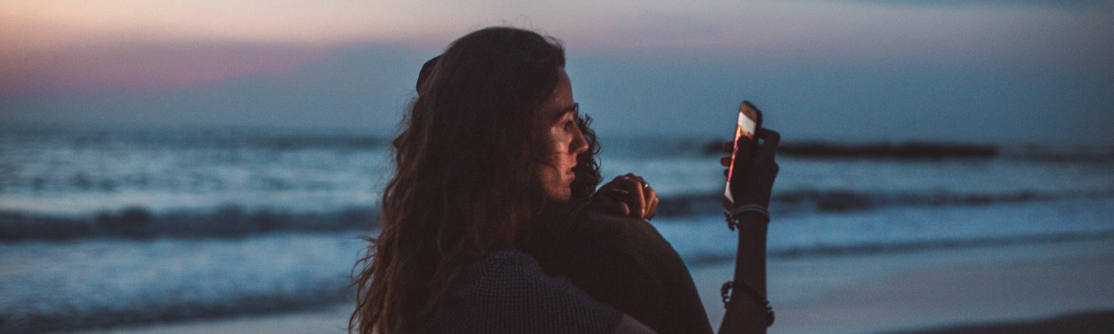 Two people hug on a beach while looking at their phones.
