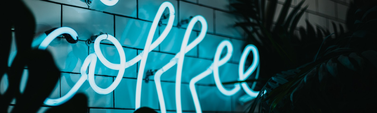 A 'coffee' sign in blue neon lights, partially obscured with silhouettes of greenery.