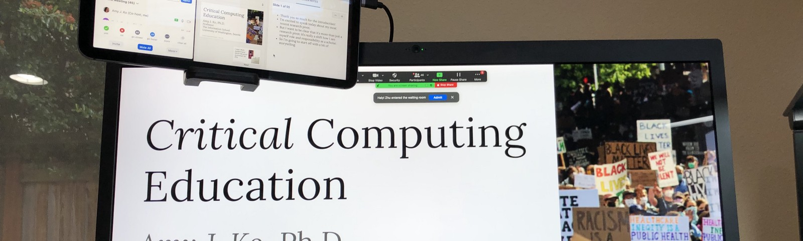 """A photograph of a display showing a slide titled """"Critical Computing Education"""", with an iPad hovering above showing Zoom."""