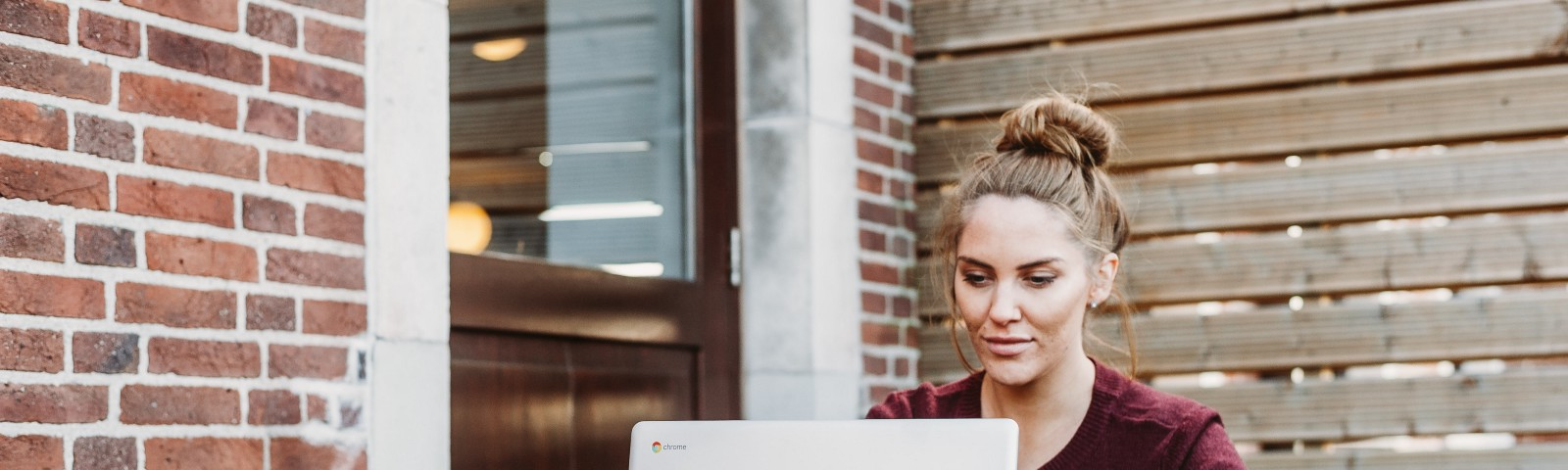 Woman sitting outside working on laptop with pot of tea.