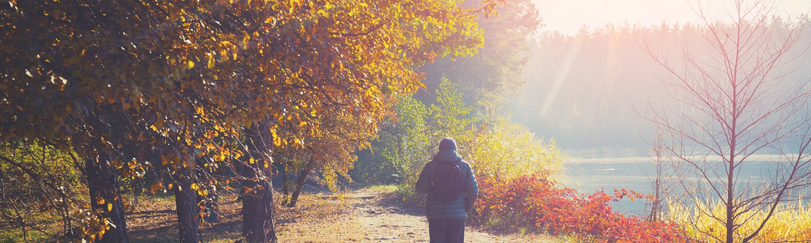 picture of a man walking on a dirt path by a river in autumn.