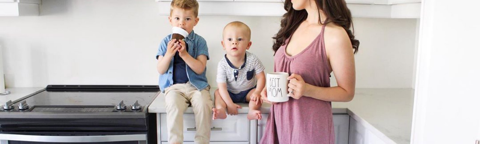 """Mother holding """"Best Mom"""" coffee mug as she stands with two young children in a kitchen."""