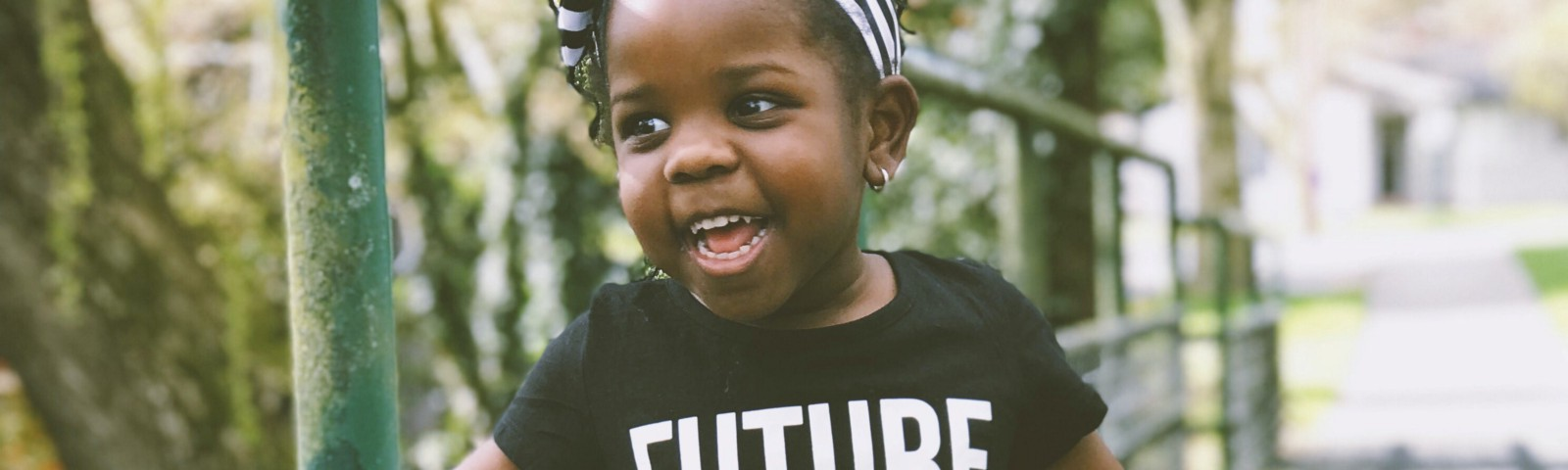 """Excited adorable kid, with brown skin and black braids in a striped headband, in a """"Future Leader"""" shirt, on a little bridge"""