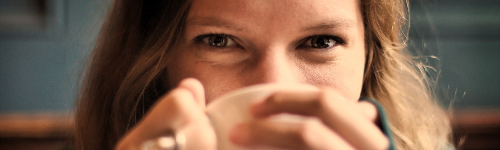 girl wearing a comfortable sweater and drinking a cup of coffee