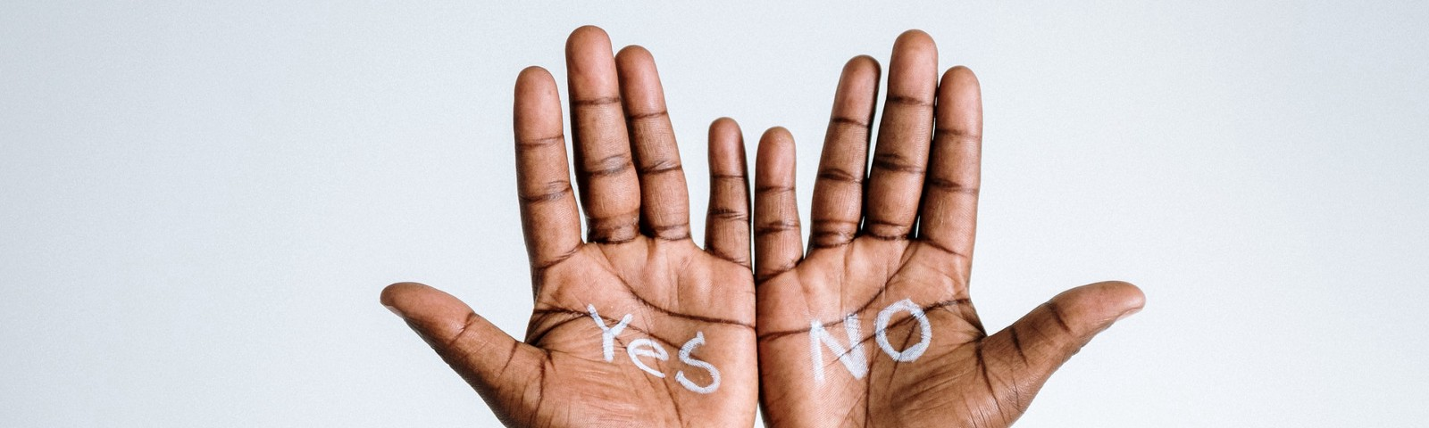 A pair of hands with yes written on the left hand and no on the right.