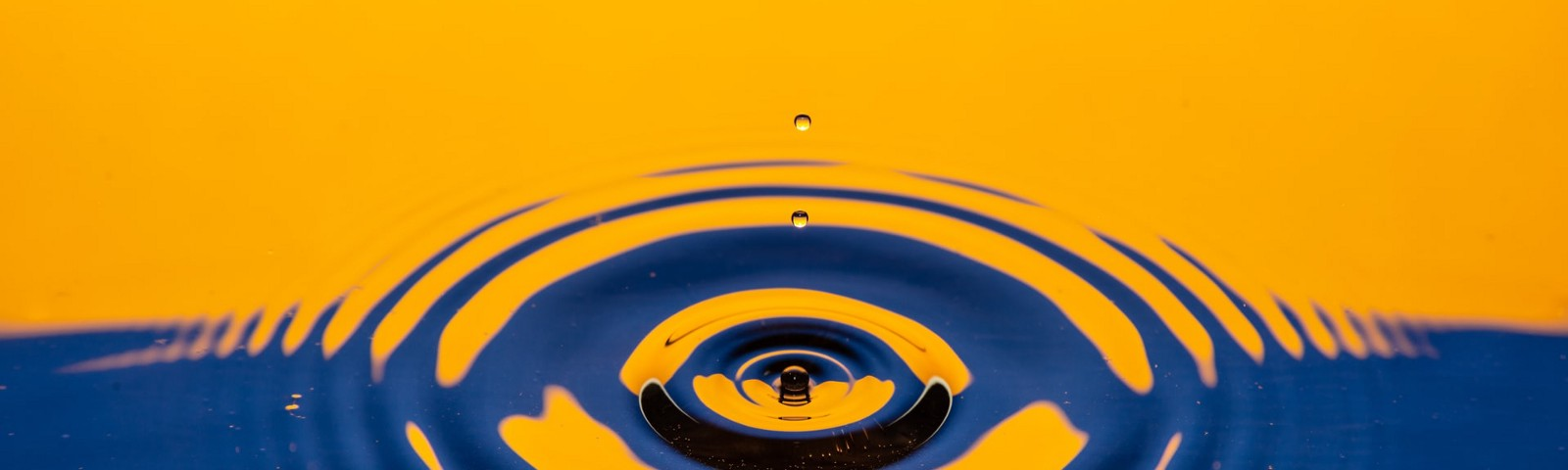 A close up of a water droplet piercing the stillness of a river reflecting orange and blue back hues.