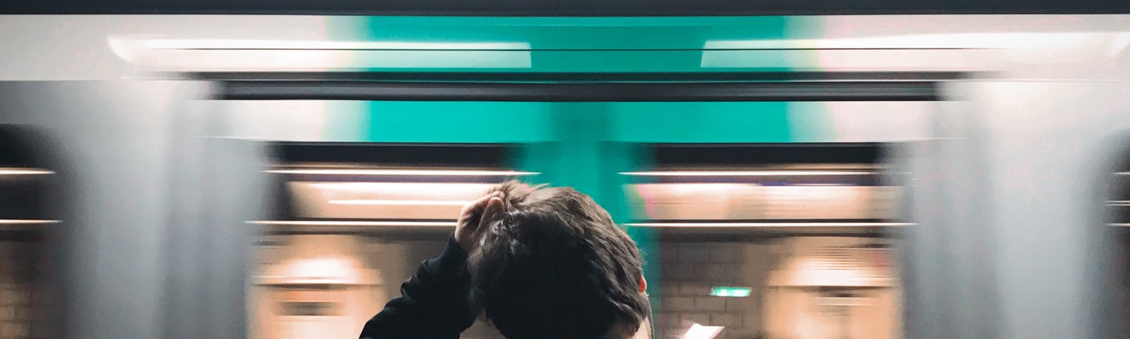 A man scratching his head as he loses focus of a train in front of him
