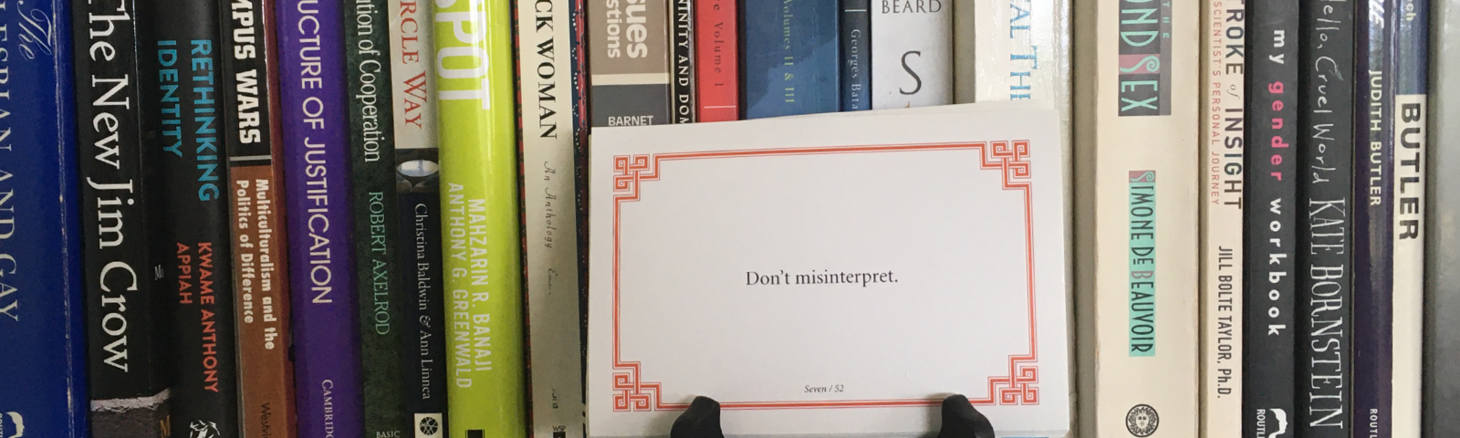 Lojong slogan card on a black card stand on a white bookshelf with books behind it. Card reads: Don't misinterpret