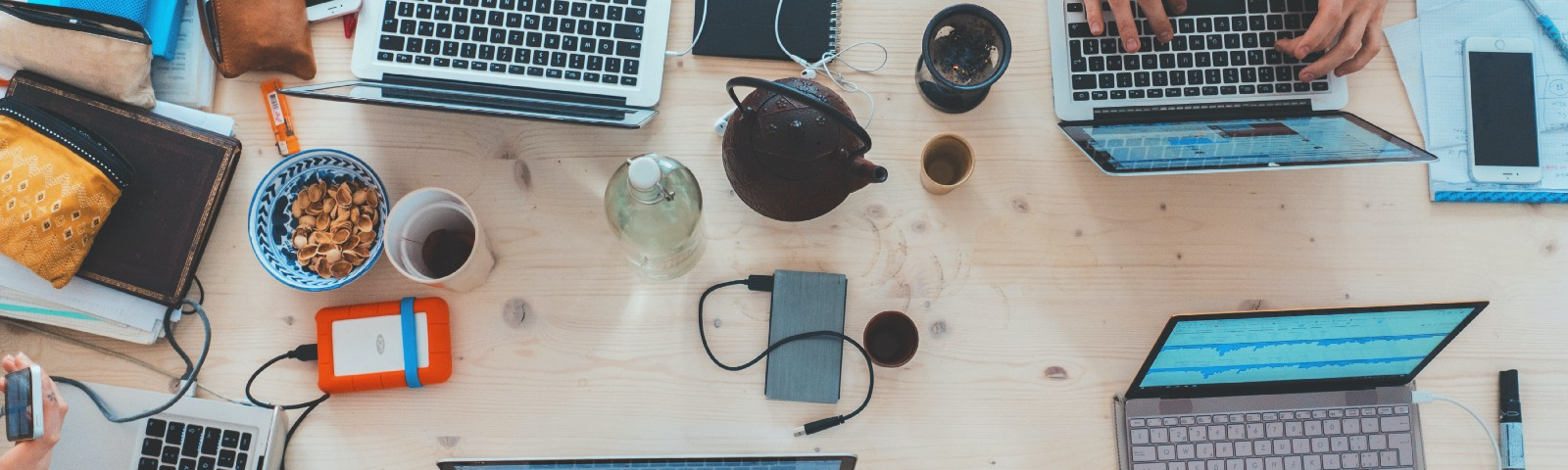 A cluttered work table covered in technology devices and snacks with 2 individuals doing work on those devices