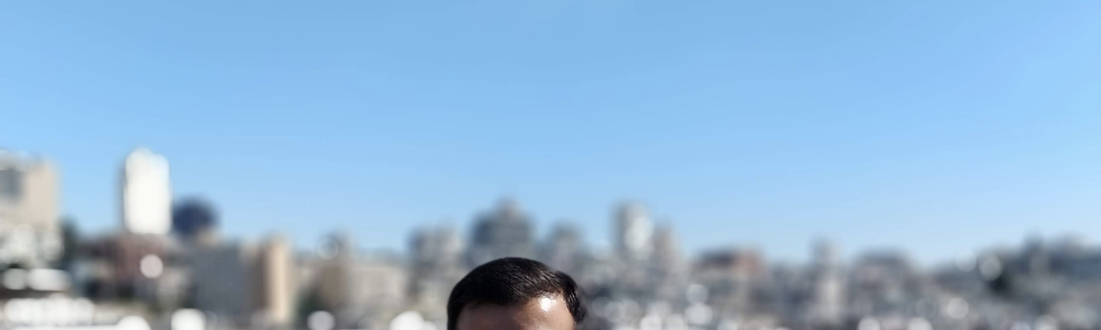 Shreyas stands smiling in front of a city skyline.
