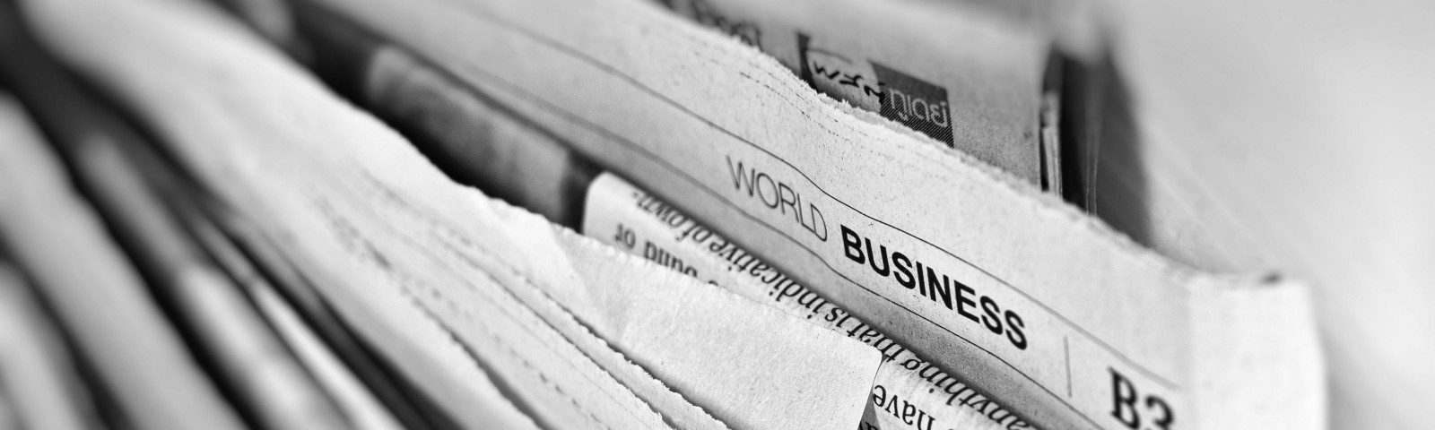 A set of broadsheet newspapers stacked horizontally with business section highlighted.
