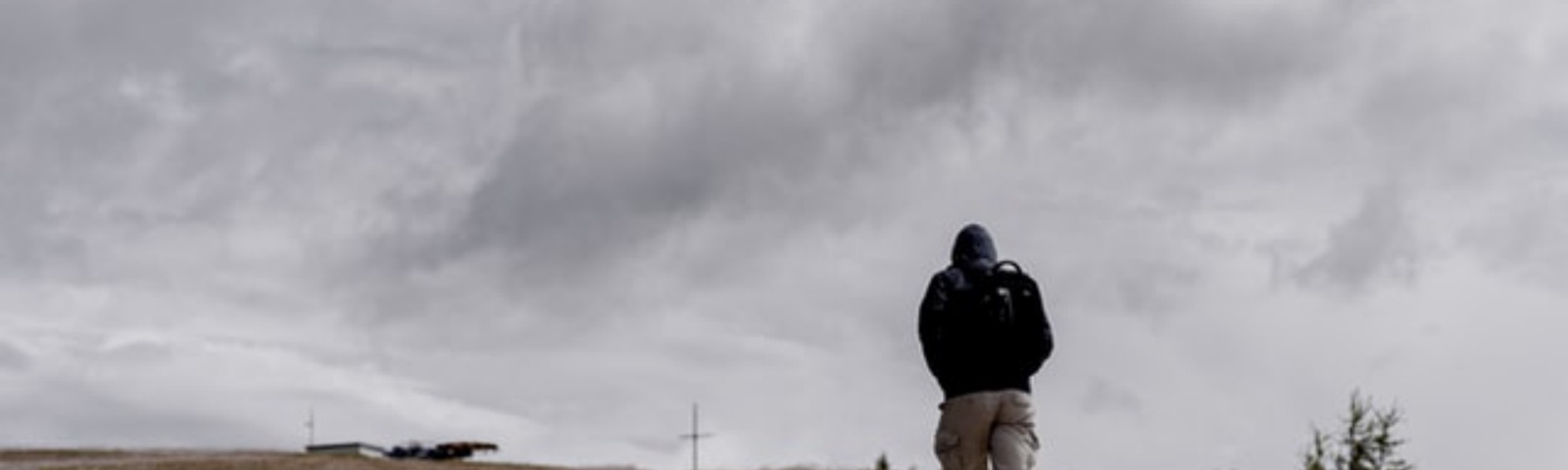 Person in black jacket and beige shorts walking under a grey sky