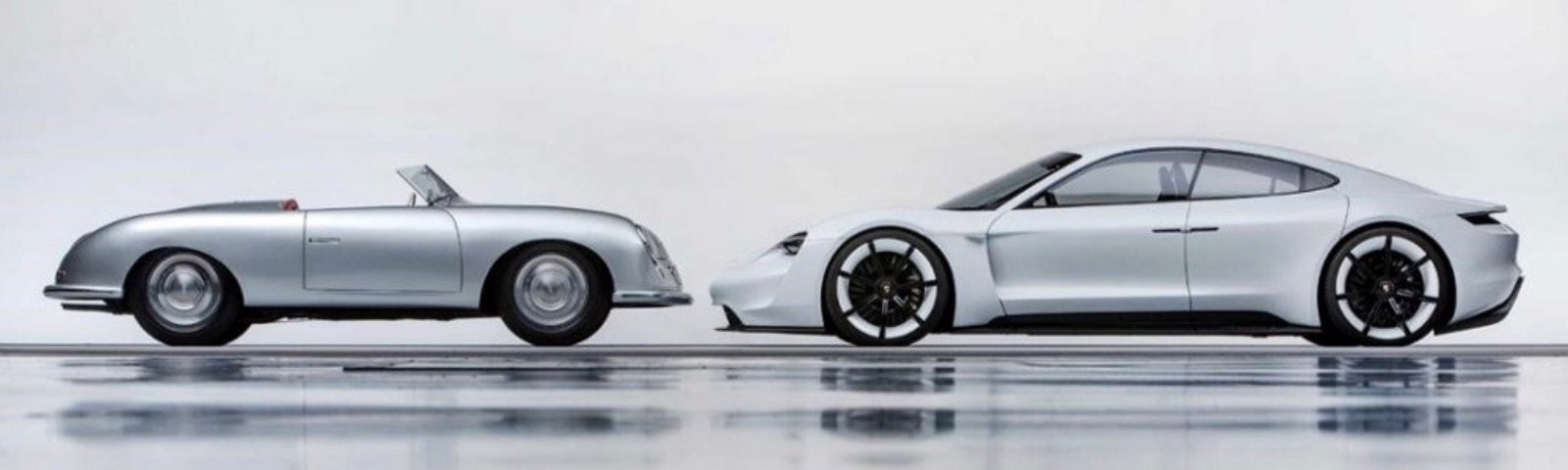 Two cars facing each other, on the left an old Porsche 356, on the right the electric prototype Mission E of 2018