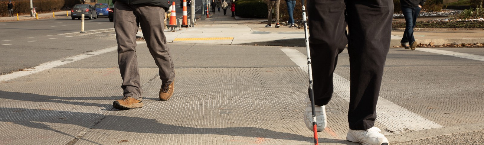 Two people crossing an intersection with the image taken from a low angle showing the curb ramp. One person uses an assistive can typically used by people with visual impairments.