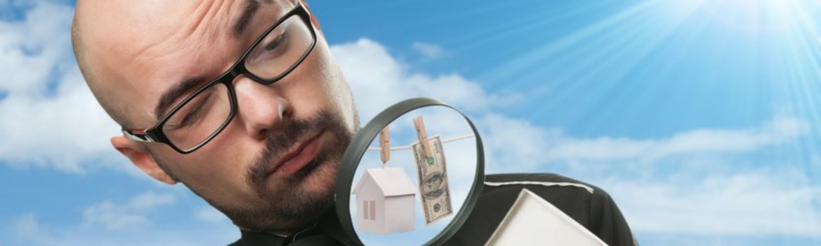 Man with magnifying glass looks closely at toy house.