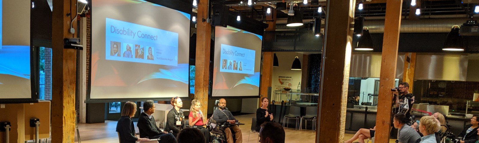 4 panelists, a moderator, and an ASL interpreter sit in front of an audience during Disability Connect at Adobe SF.