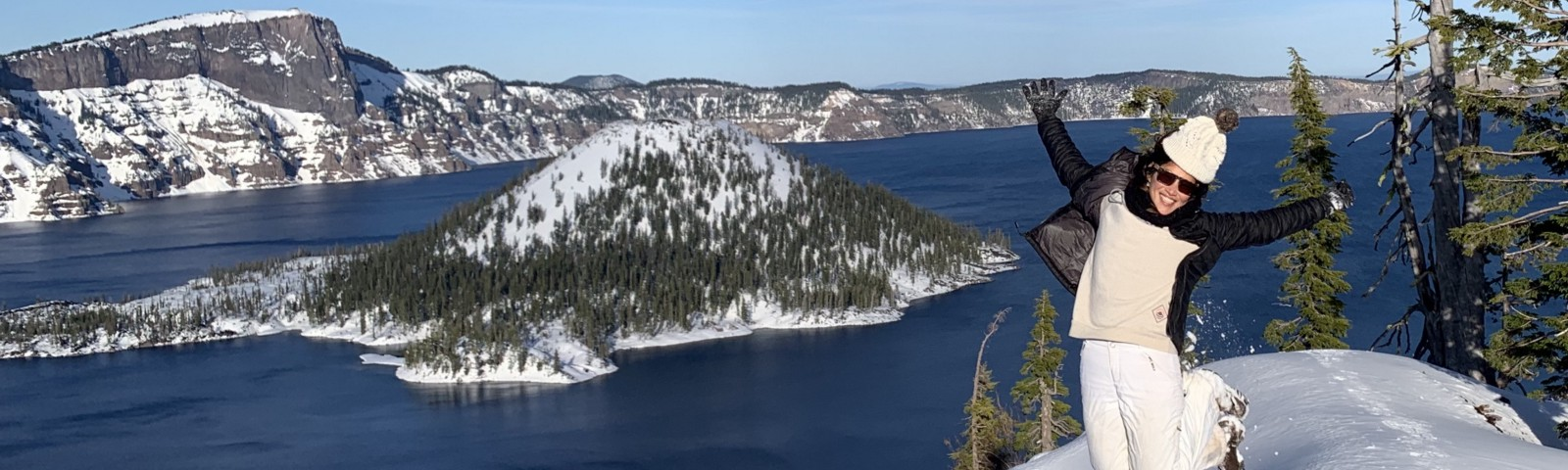 The author jumping high over the snow at the edge of Crater Lake, OR
