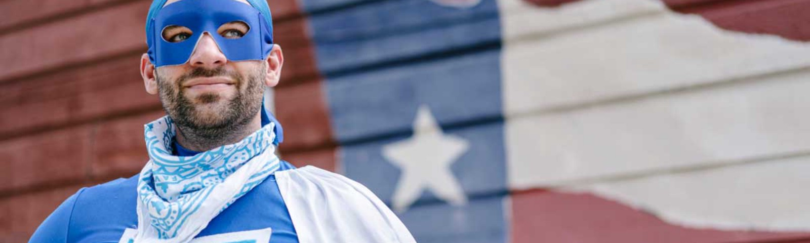 """Man wearing a blue """"Favorman"""" super hero costume standing in front of a Texas flag"""