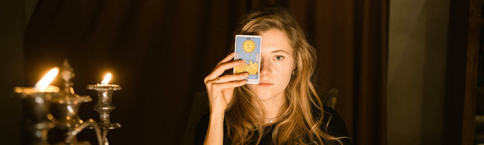 Woman holding tarot card up to her face