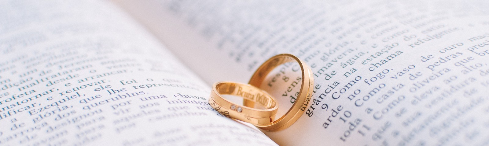 Two wedding rings nestled together inside an open Spanish Bible