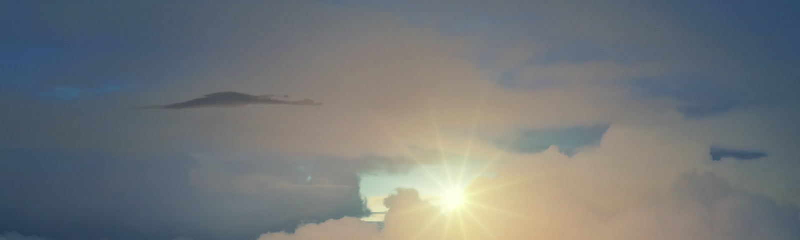 Photo of sun cutting though clouds and surreal window of blue sky.