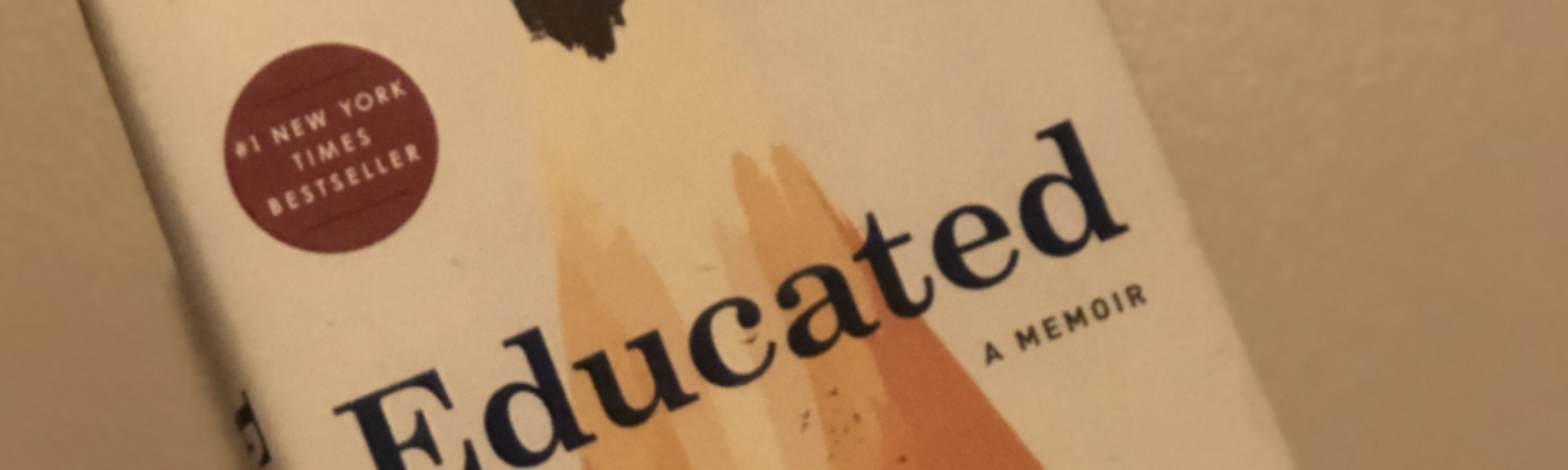 Hand holding up Educated by Tara Westover against a tan wall