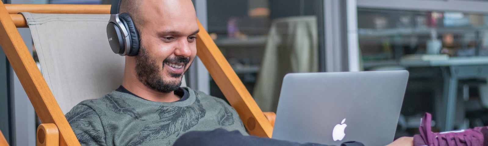 Man sitting on a chair smiling while working on a laptop and using headphones