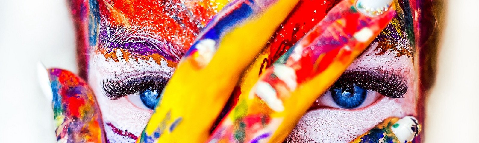 Close up of a face with a hand covering it. The face and hand are covered in red, yellow, and blue paint