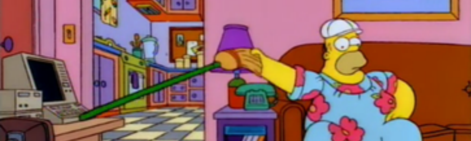 Homer Simpson watching TV while using a broomstick to hit his keyboard across the room.