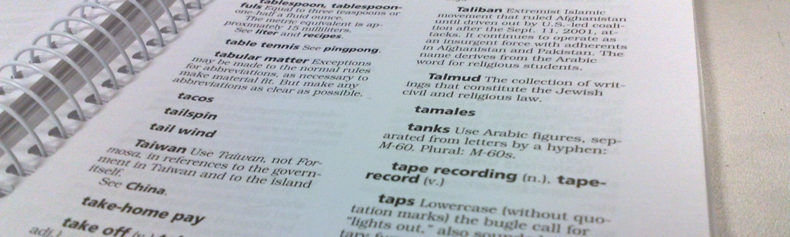 Spiral AP Stylebook open to first page of T section.