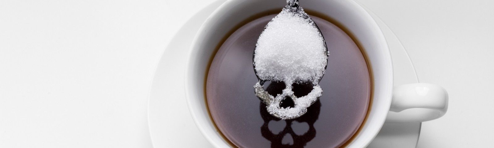 Coffee with a spoonful of sugar, the sugar shaped to look like a skull.