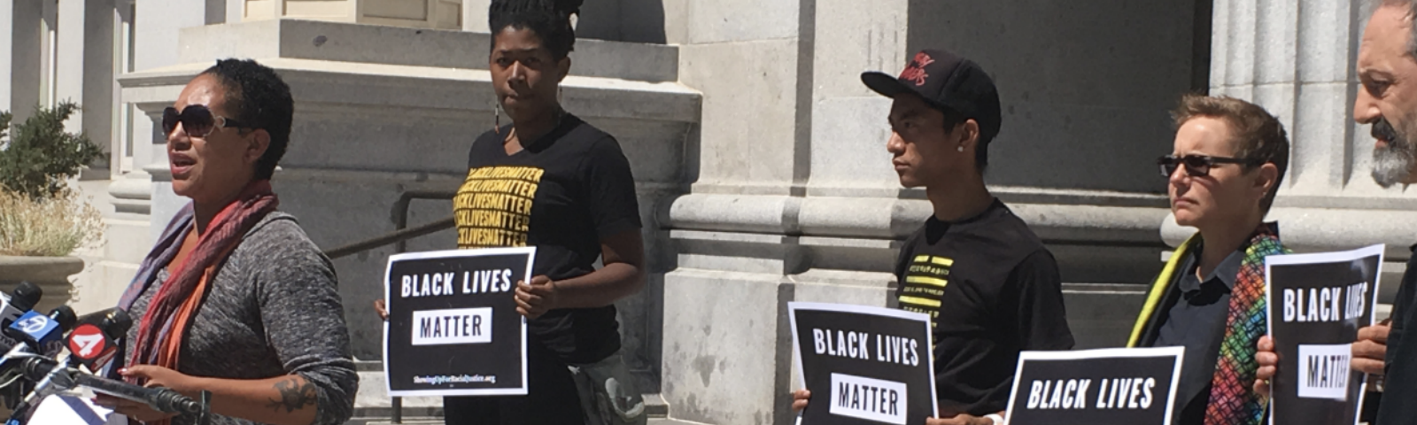 """Cat brooks speaks at a mic in front of a grey building; 4 people holding """"Black Lives Matter"""" signs stand behind her"""