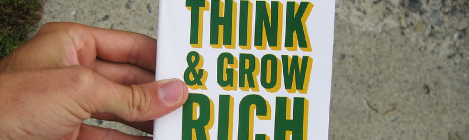 A hand holding the book by Napoleon Hill, Think & Grow Rich.