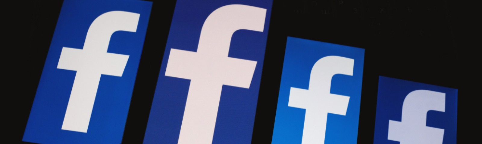 Facebook logos are displayed on the screen of the smartphones.