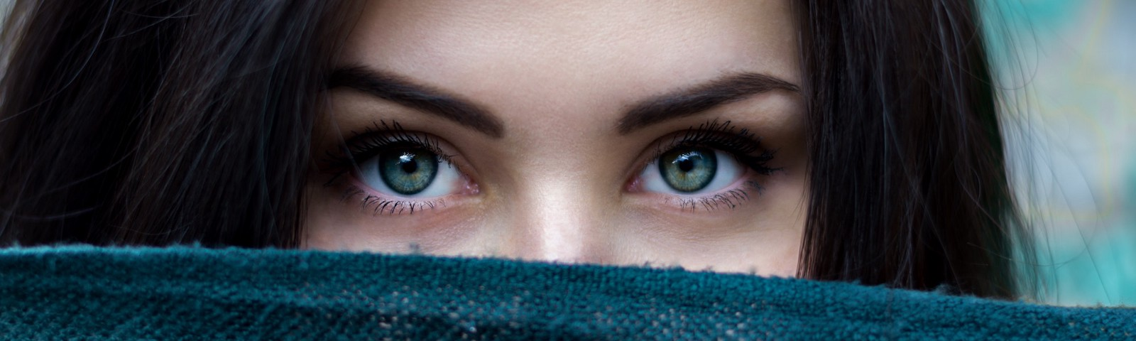 woman looking over a scarf in front of her face
