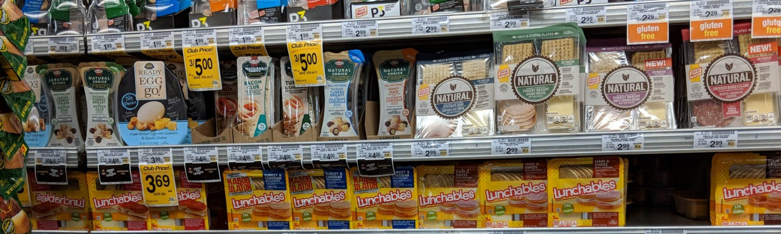 A display at a grocery store of various lunch kits, including Lunchables.