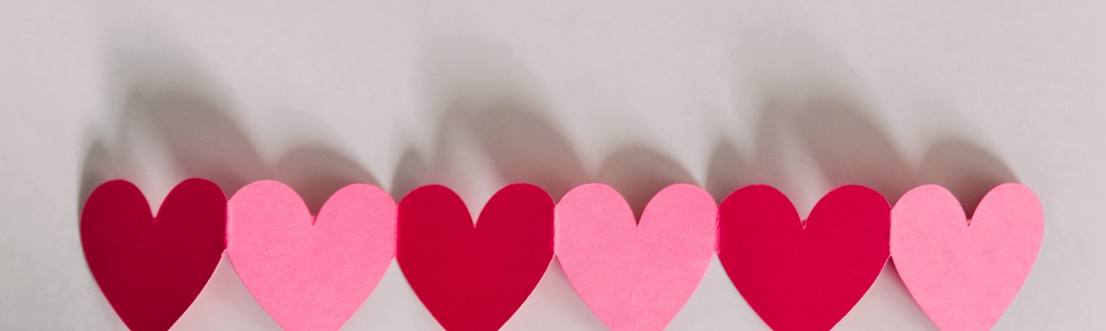 Pink and red paper hearts placed in a row