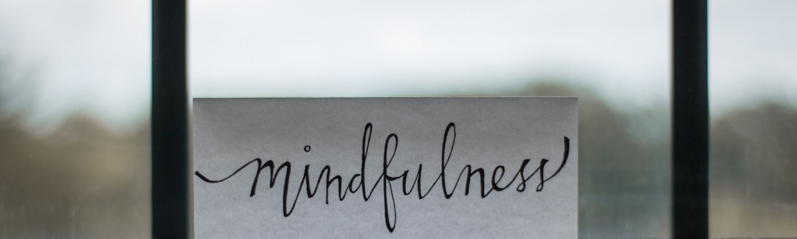 The word mindfulness written on a piece of paper by a window
