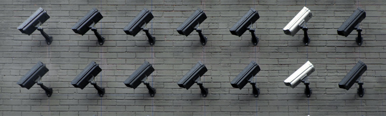 multiple CCTV cameras on a wall