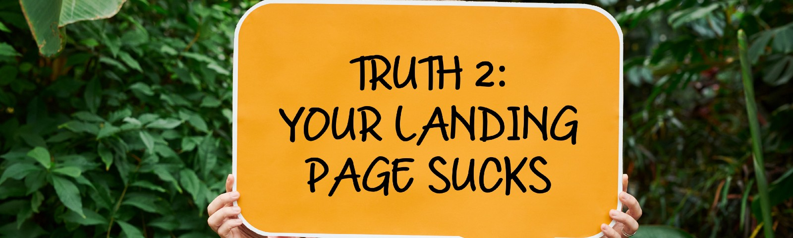 """Woman holds up """"your landing page sucks"""" sign."""