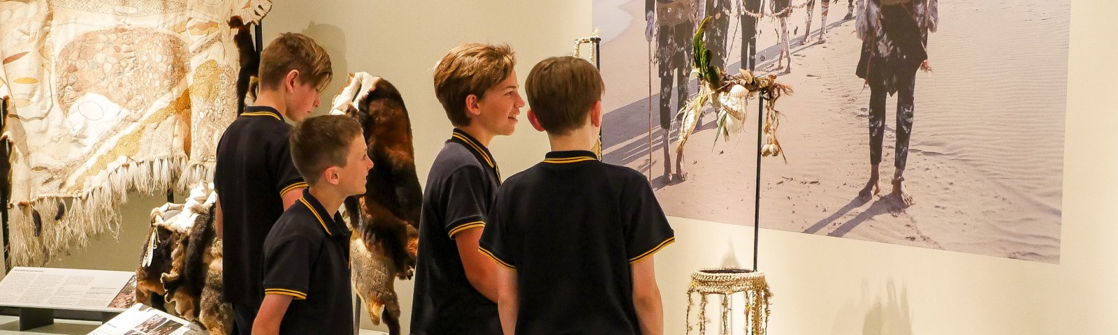 Four boys in navy school uniforms look at a museum display of headpieces decorated with feathers and shells.