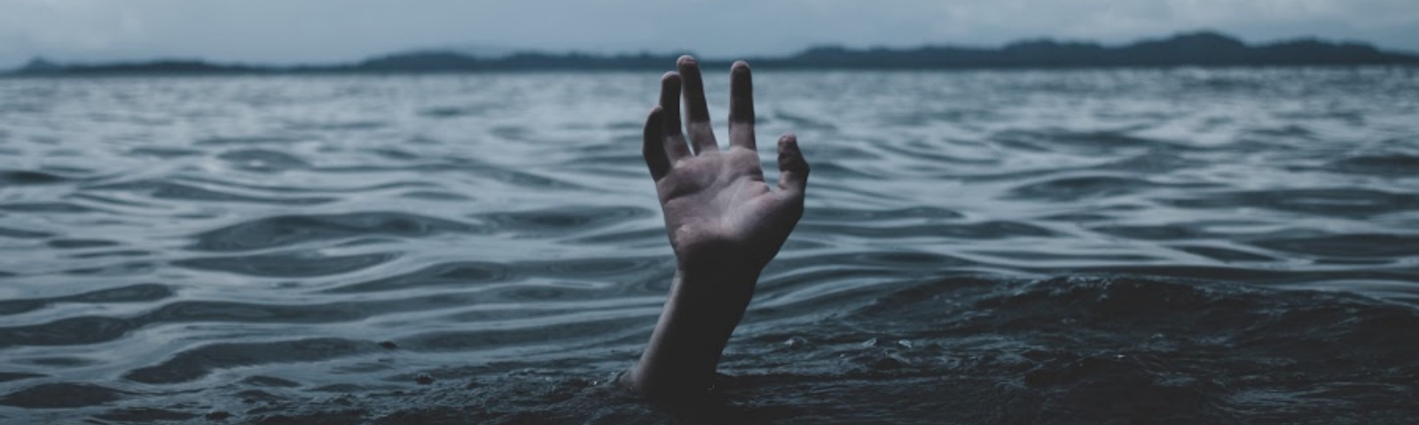 Man drowning, with only his hand remaining above water.