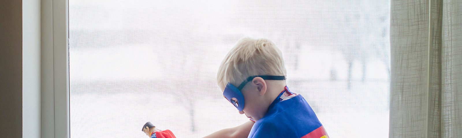 A small blonde-haired boy with a superman cape over his back, and a mask over his eyes sitting on a windowsill holding a superman action figure with his right hand.