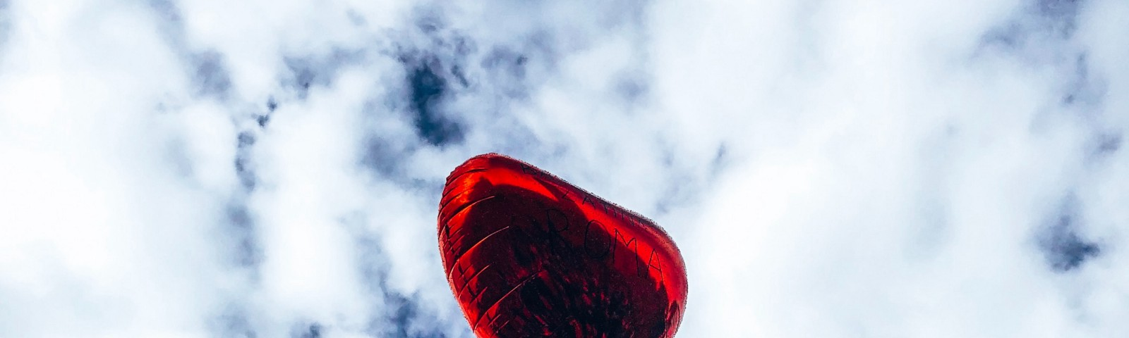 Red mylar heart balloon up in the blue sky surrounded by white fluffy clouds