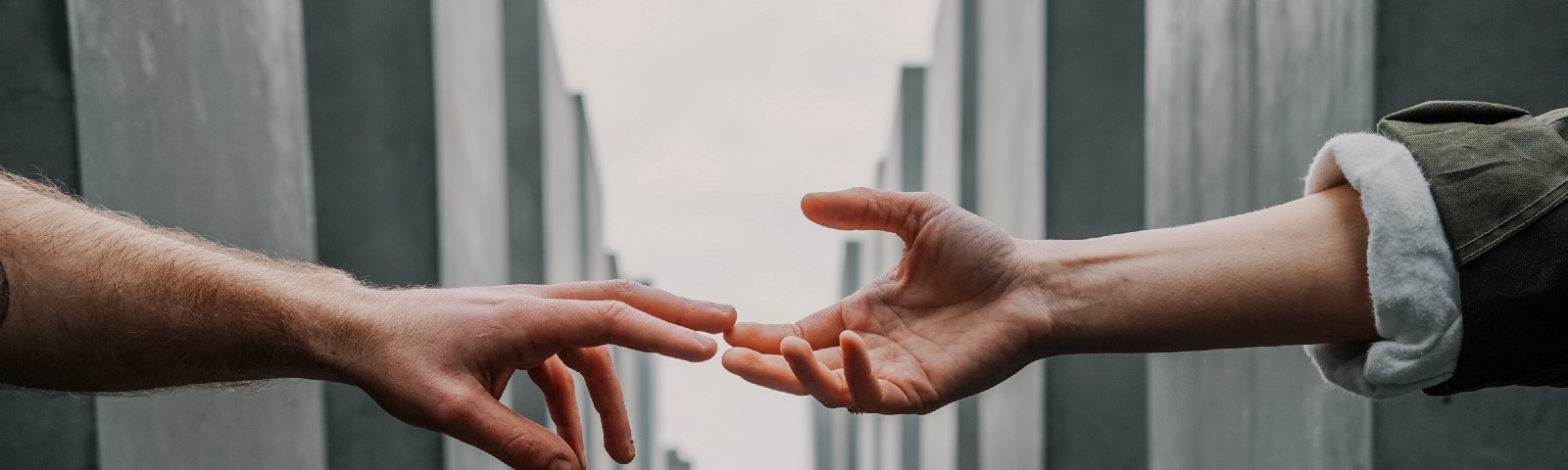 Two hands reaching out to each other, with slabs of concrete in the background