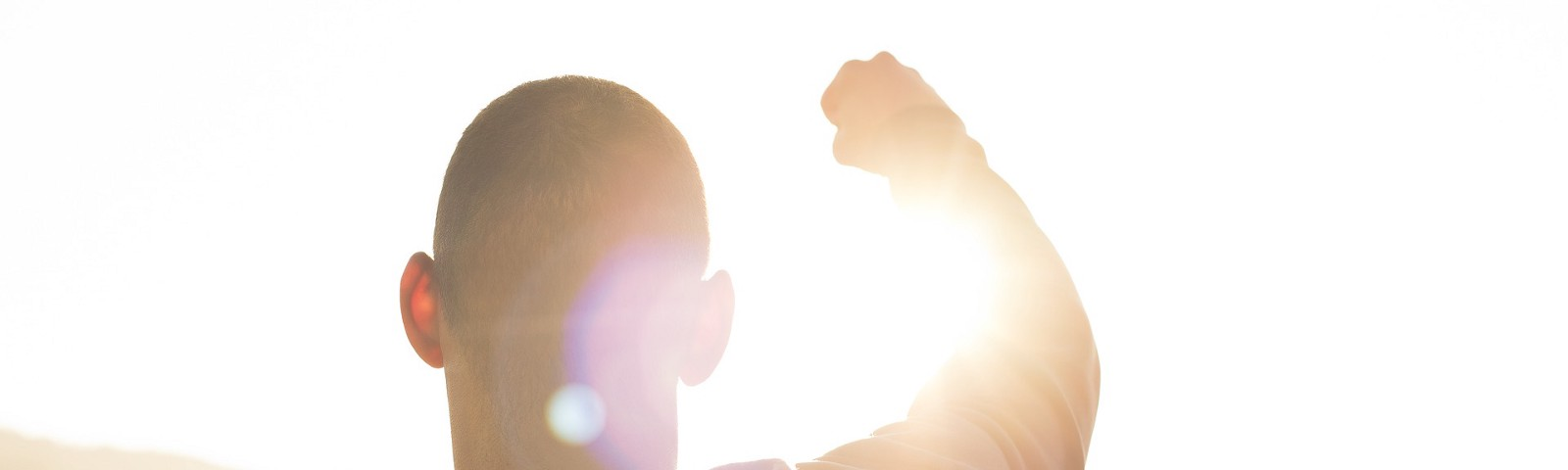 a man with victorious fist upraised with the sun shining