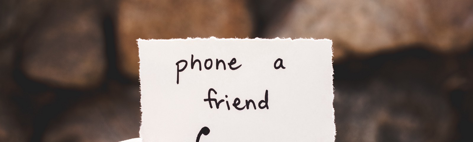 "A hand holding a piece of paper with ""phone a friend"" written on it and a symbol of a phone."