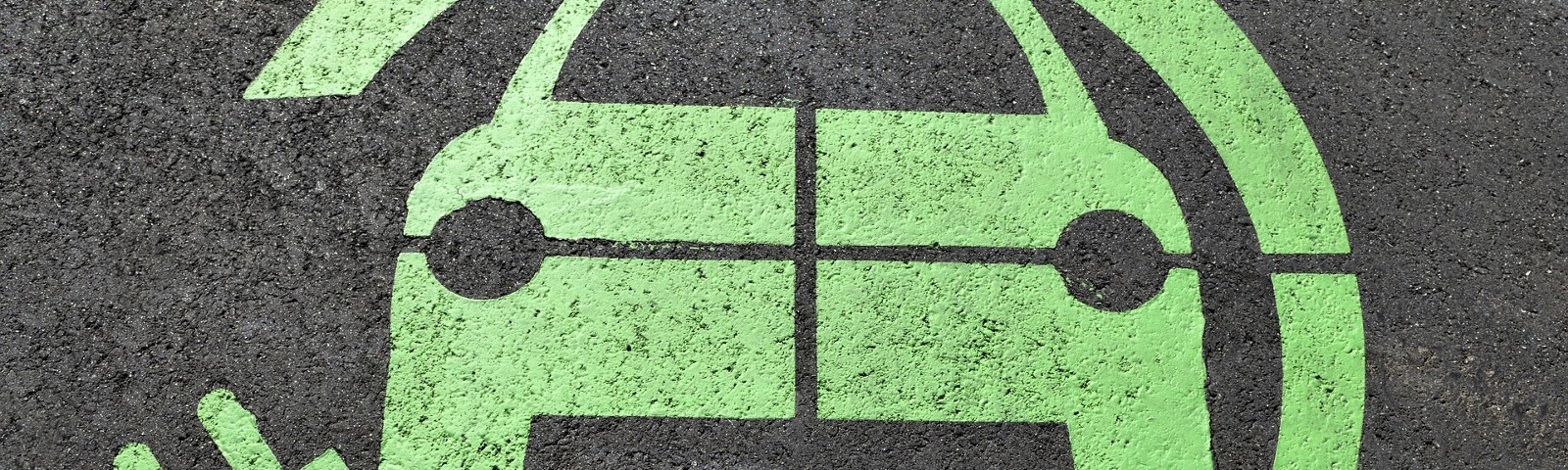 A green electric vehicle charging sign on a parking space
