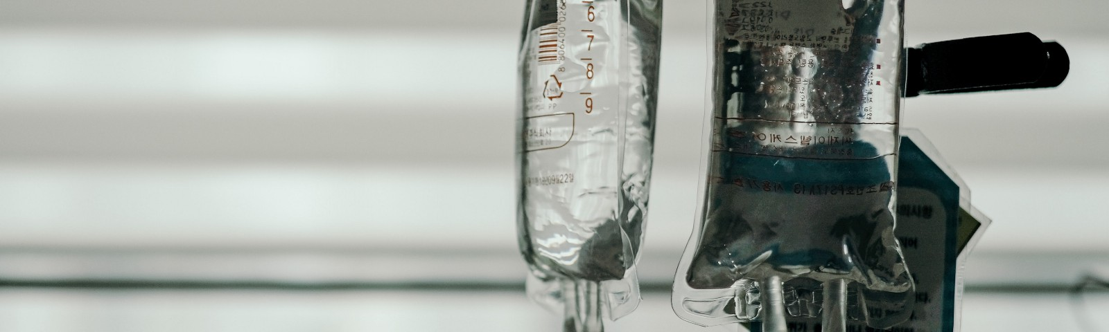 Black and white photo of intravenous fluid bags hanging on rack.