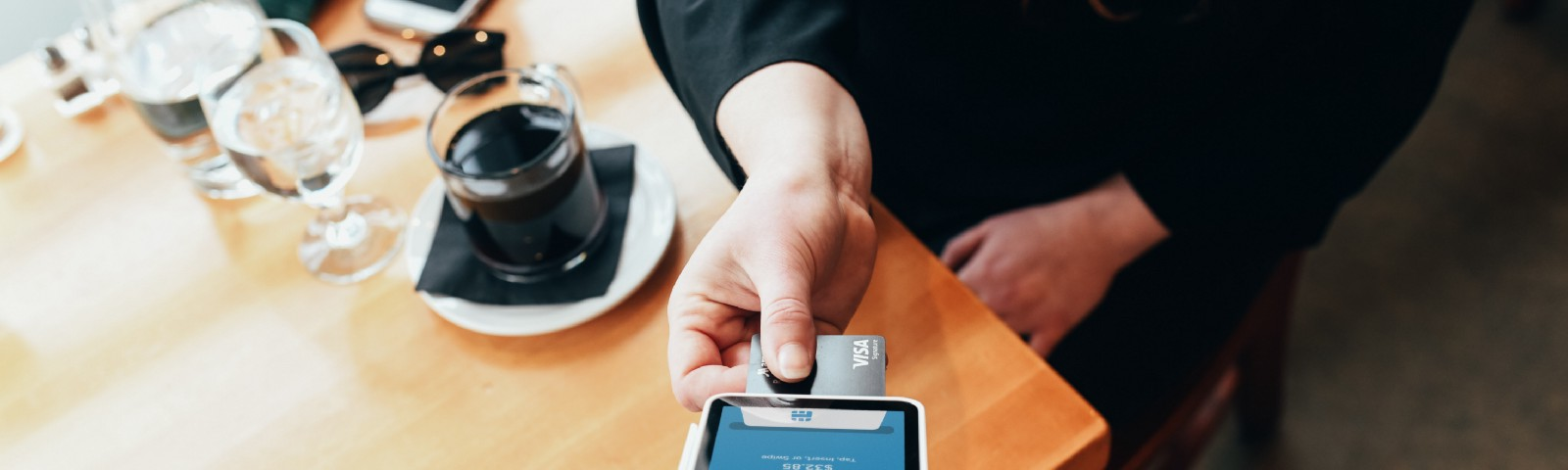 Customer using mobile payment tech in a coffee shop.